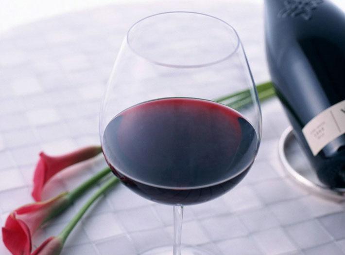"""首先把葡萄酒从瓶中倒入酒杯,用手轻端杯座,将酒杯中的酒作上下左右轻摇并转动,看酒是否挂杯(Tears of glass)。好的葡萄酒,特别是甜的白葡萄酒,一定会挂杯;其次,把酒杯放在鼻尖下吸一吸,以辨别它的香味;最 后,把酒杯轻轻放到嘴唇边微啜。这是品酒的主要的一部分,然后用舌尖来辨别酒的优劣。    上述这三种基于动作,一定要做得标准,才能显出""""行家""""品酒的风度!此外,品酒杯不需要豪华而带色,有色的杯子不易看出酒的颜色。而酒杯要干净而透明,倒酒不应太满,只倒入酒杯深度的1/3就可以了。"""